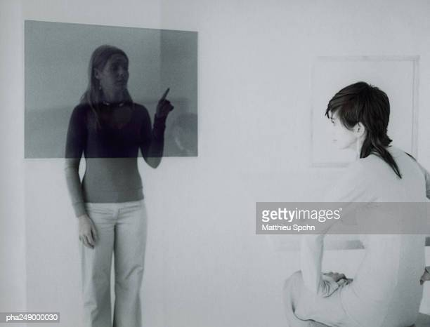 woman sitting, other woman touching translucent screen - overheadprojector stockfoto's en -beelden