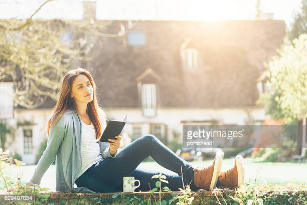 Woman sitting outdoors and reading a book
