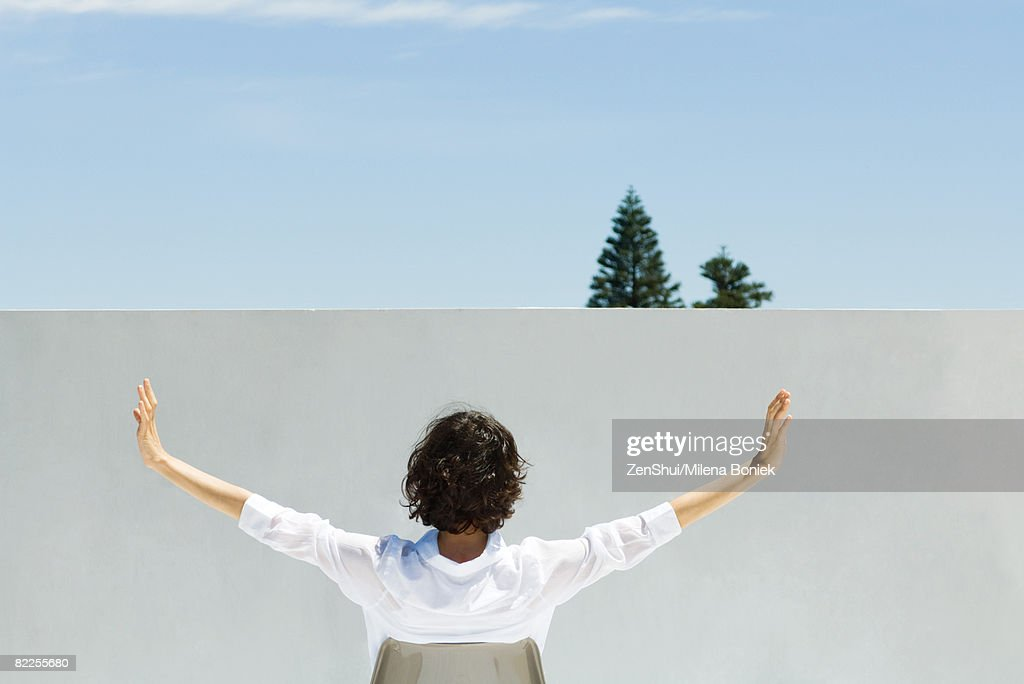 Woman sitting outdoors, arms raised in the air, rear view : Stock Photo