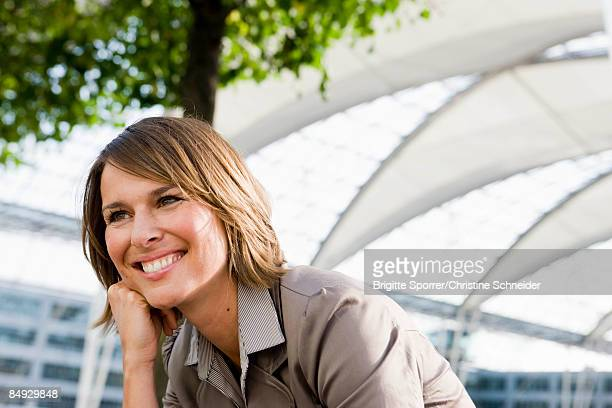 woman sitting outdoors smiling - munich airport stock photos and pictures