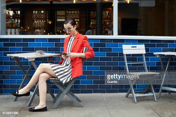 Woman sitting outside a cafe using smartphone, side view