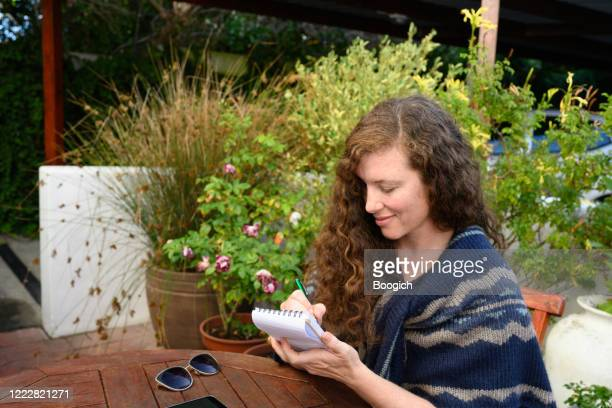 woman sitting outside house writting with a paper notepad in south africa - handwriting stock pictures, royalty-free photos & images