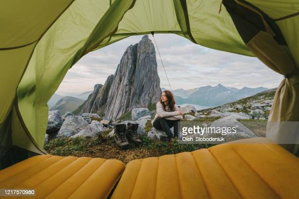 woman sitting outside of tent in  senja island in  mountains - northern norway stock pictures, royalty-free photos & images