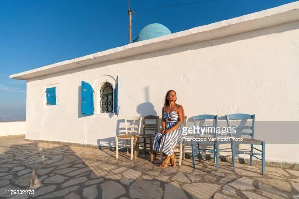 woman sitting outside the church of the profitis ilias - church of the prophet elias, lefkada, greece. - long dress stock-fotos und bilder