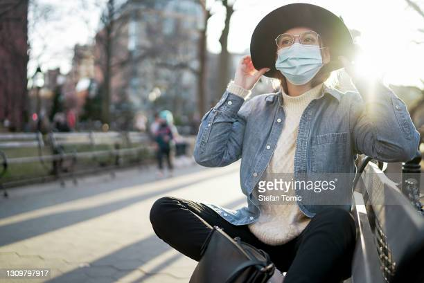 woman sitting outside with surgical face mask on park bench at sunset - washington square park stock pictures, royalty-free photos & images