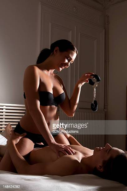 Woman sitting over a man in bed, holding handcuffs