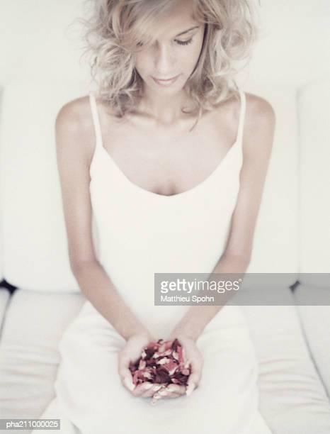 woman sitting, petals in her hands. - nachthemd stockfoto's en -beelden