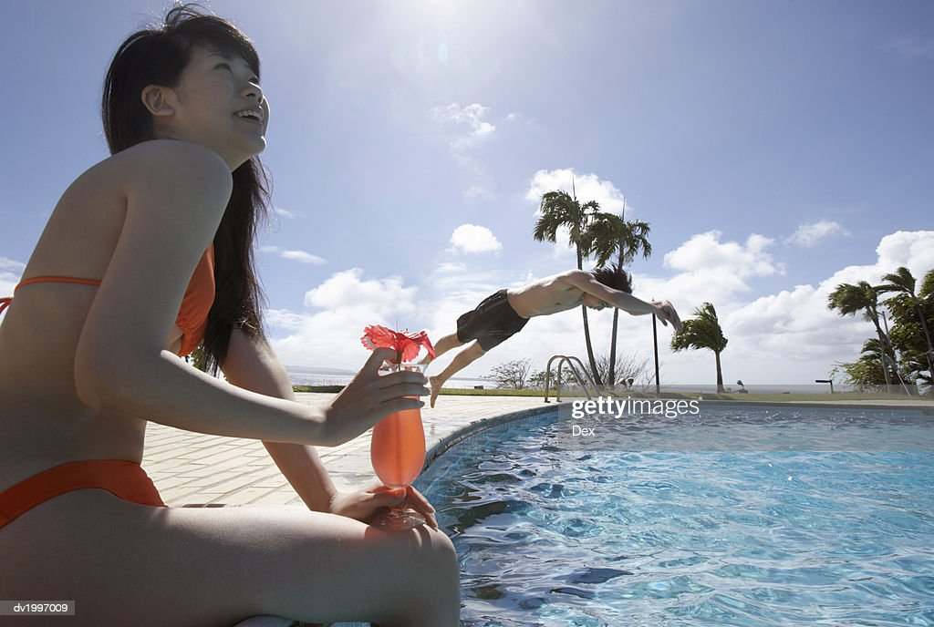 Woman Sitting Poolside Holding a Cocktail and a Man Diving into a Swimming Pool : Stock Photo