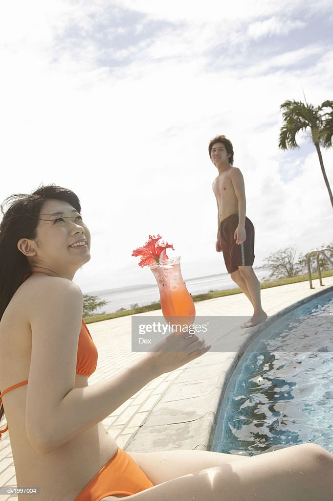 Woman Sitting Poolside Holding a Cocktail and Young Man in the Background : Stock Photo