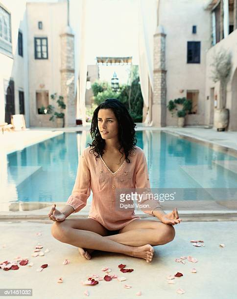 woman sitting poolside in the lotus position with petals around her, marrakesh, morroco - femme marocaine photos et images de collection