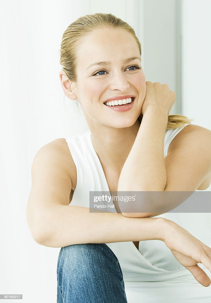 Woman sitting, resting arm on knee, smiling : Stock Photo