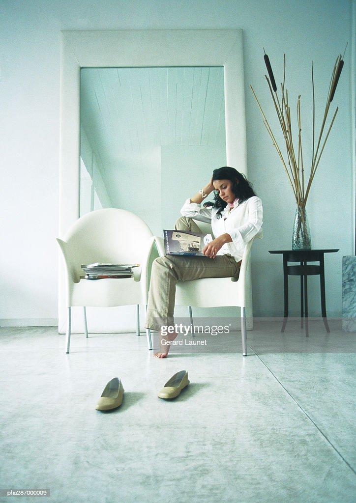 Woman sitting sideways in chair, looking through magazines : Stockfoto
