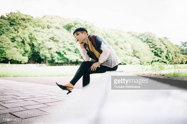 woman sitting sideways - yusuke nishizawa stock pictures, royalty-free photos & images