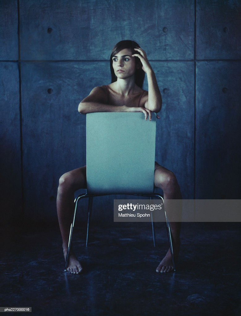 Woman sitting straddled, hand to head. : Stockfoto