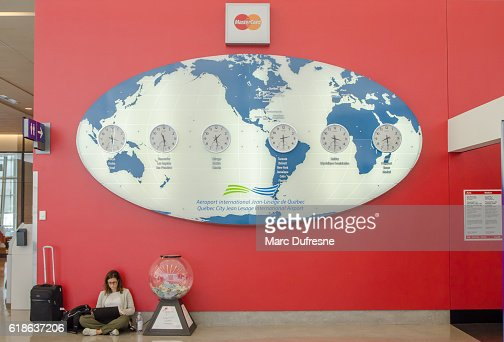 Woman sitting under large world map with international clocks stock woman sitting under large world map with international clocks stock photo getty images gumiabroncs Image collections