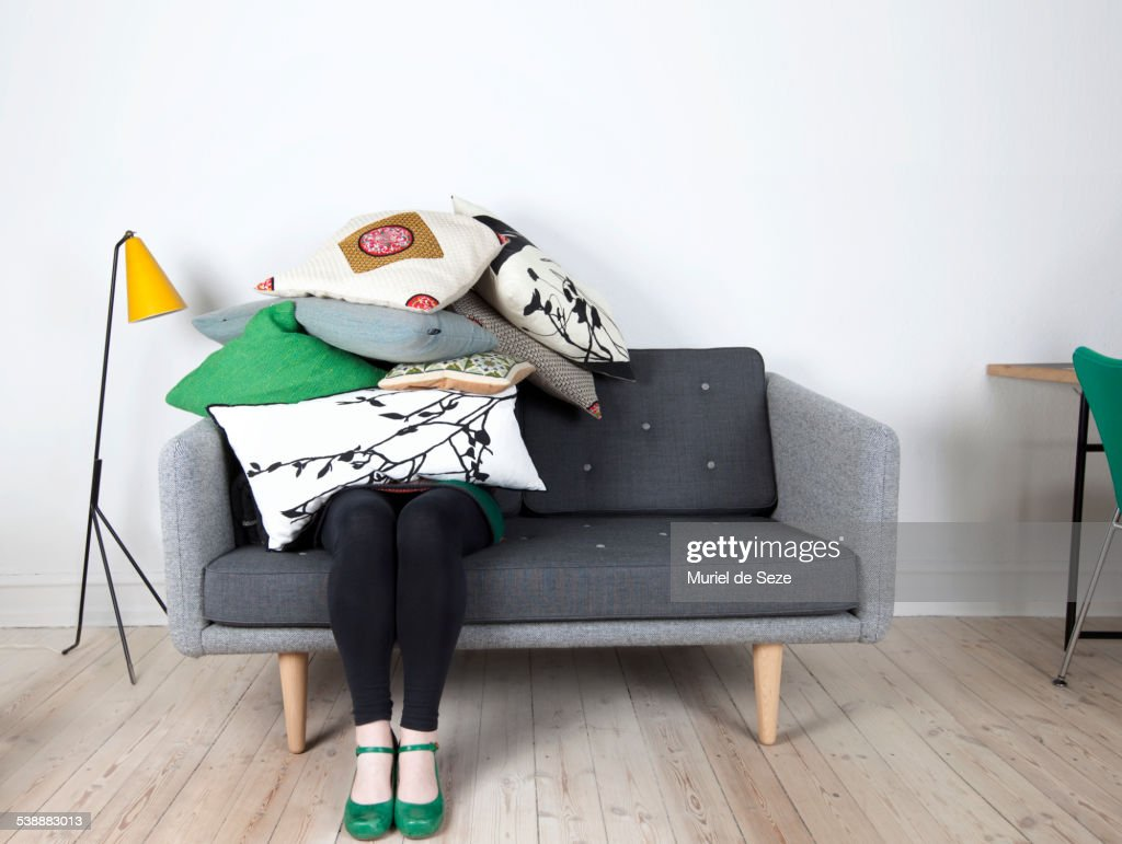 Woman sitting under pile of pillows : Stock Photo