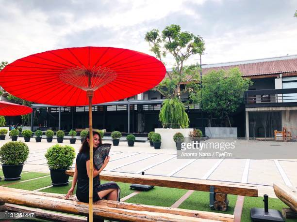 Woman Sitting Under Red Umbrella In City