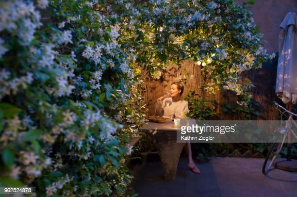 woman sitting under star jasmine pergola at dusk, enjoying her book and glass of wine - romantiek begrippen stockfoto's en -beelden