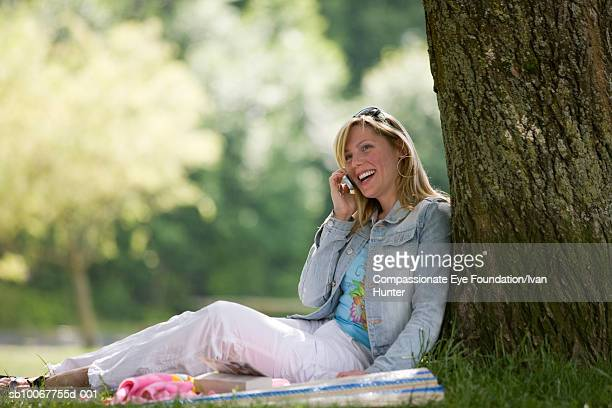 Woman sitting under tree on sunny day with mobile phone