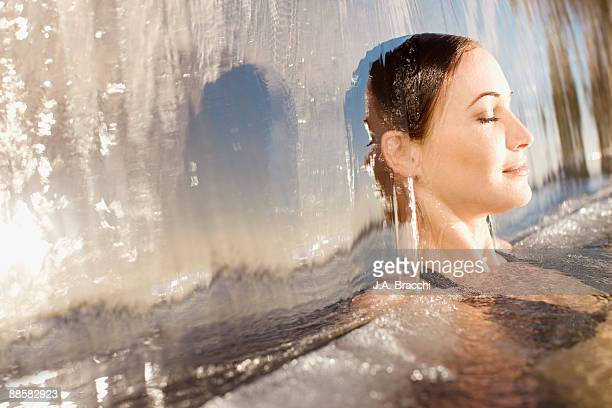Woman sitting underneath waterfall