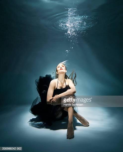 Woman sitting underwater, looking up