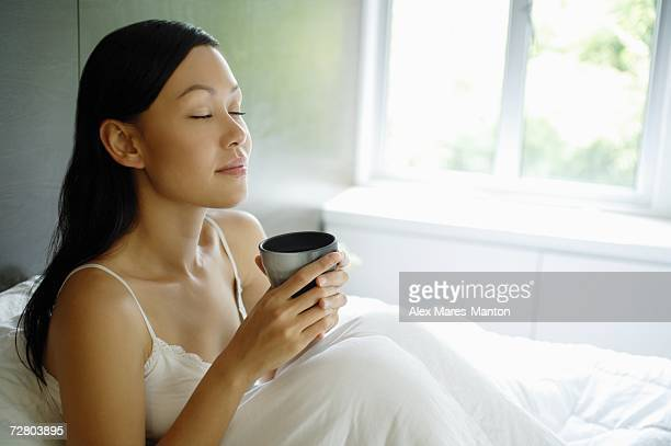 Woman sitting up in bed, holding cup, eyes closed