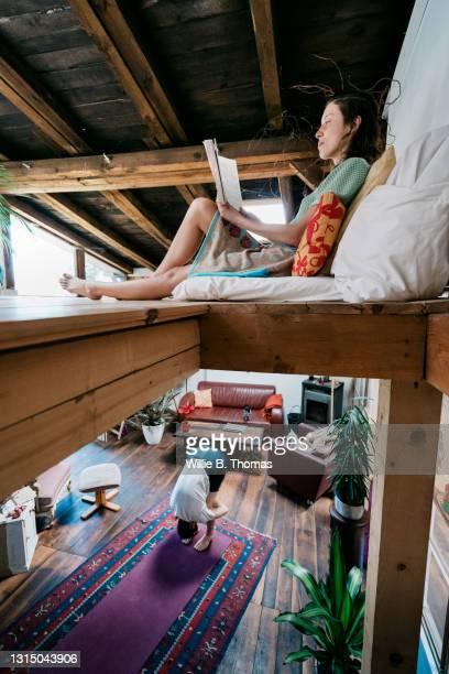 woman sitting up on mezzanine while partner is downstairs - mezzanine photos et images de collection