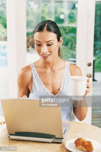 Woman Sitting Using Laptop and Eating Breakfast