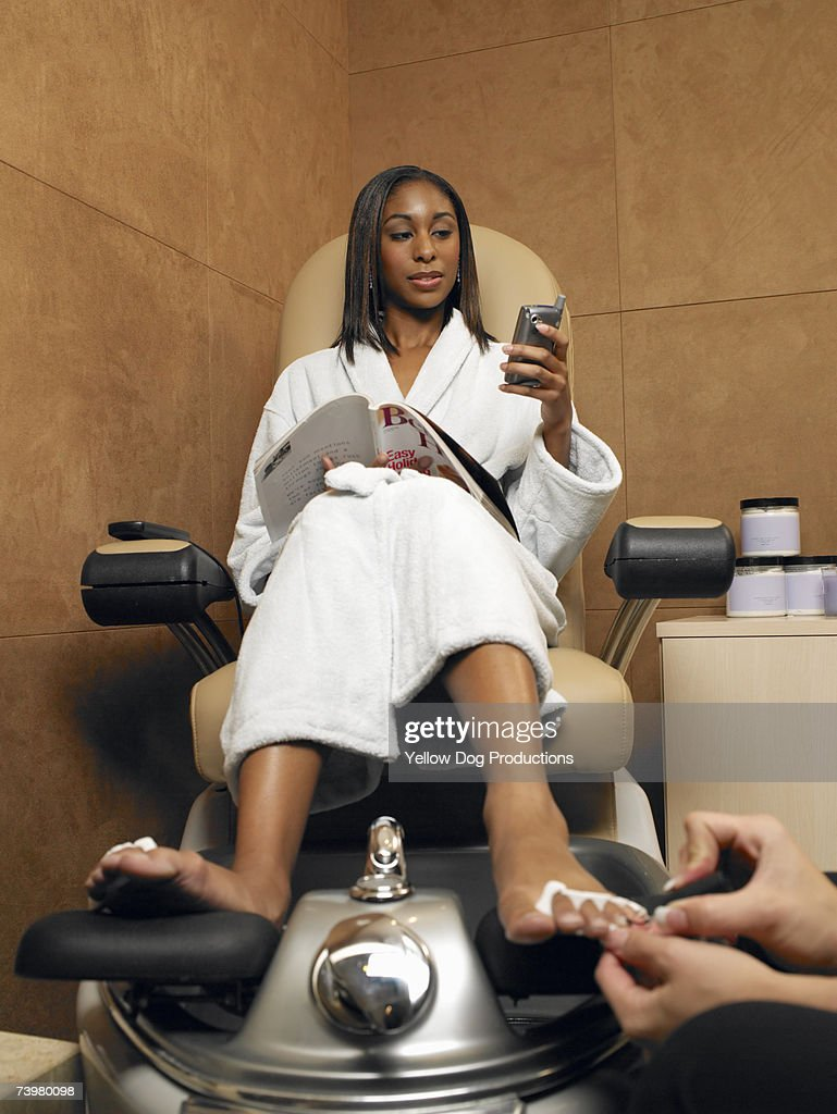 Woman sitting using mobile phone having pedicure : Stock Photo