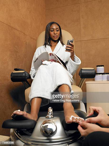 Woman sitting using mobile phone having pedicure