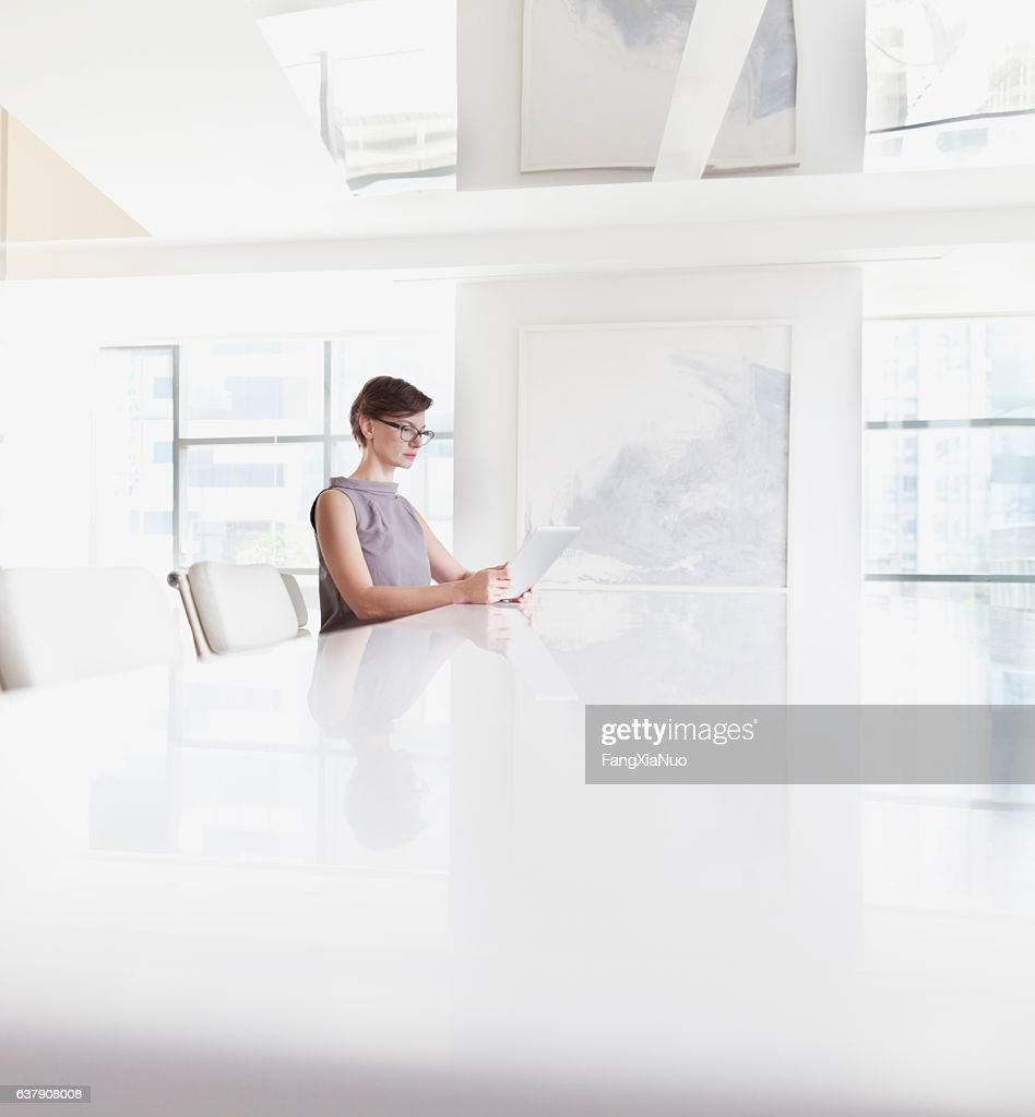 Woman sitting using tablet computer in room : Stock Photo