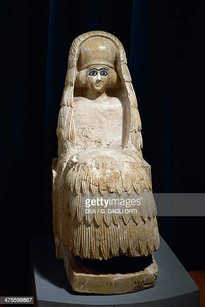 Woman sitting wearing kaunakes fleece cloak made from goat hair or wool and a polos headdress with veil alabaster statue from the Temple of Ishtar at...