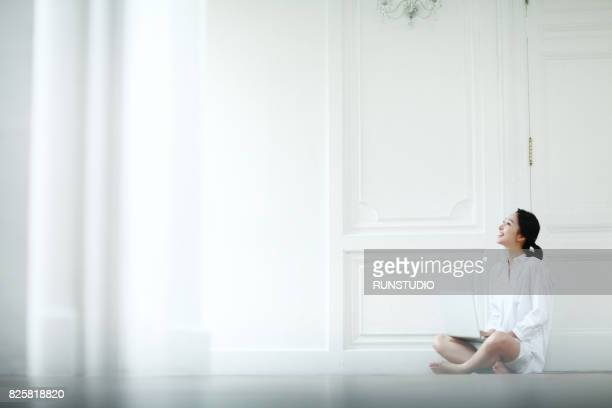 woman sitting with a laptop in the house
