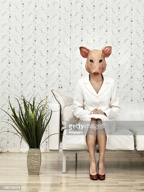 Woman sitting with a pig mask
