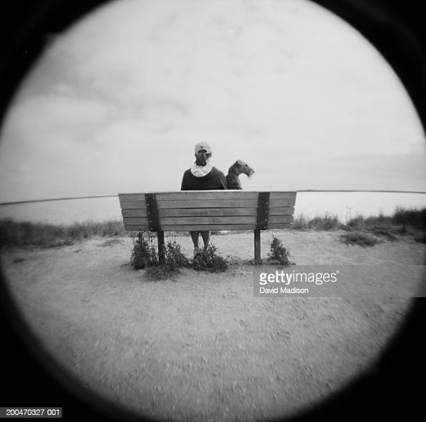 Woman sitting with Airedale Terrier on bench (fisheye, B&W), rear view