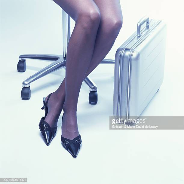 Woman sitting with ankles crossed, by metal briefcase, low section