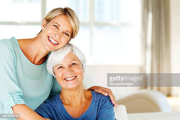 Woman Sitting With Arm Around Mother In Living Room