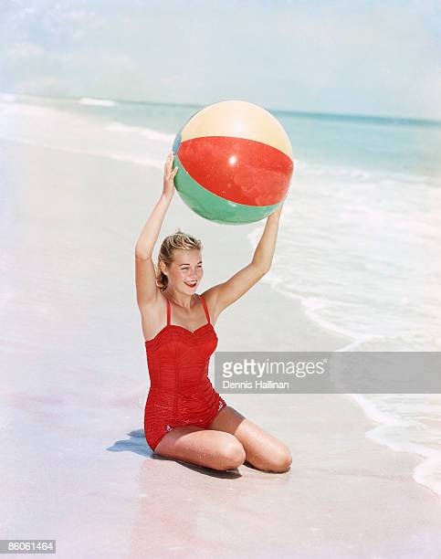 Woman sitting with beach ball by ocean