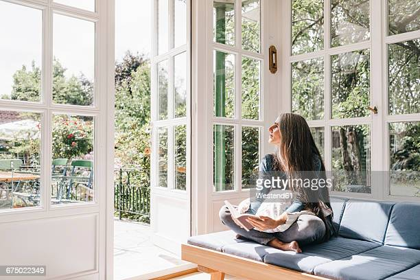 Woman sitting with book on lounge in winter garden looking through opened terrace door
