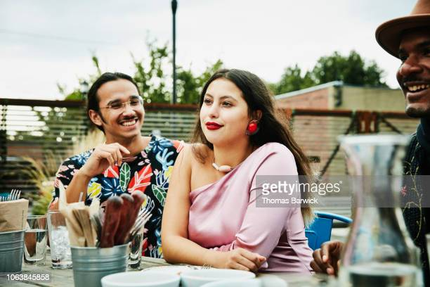 woman sitting with boyfriend during party at outdoor restaurant - heterosexual couple stock pictures, royalty-free photos & images