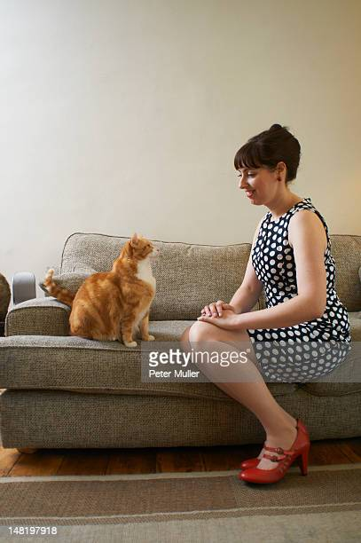 Woman sitting with cat on sofa