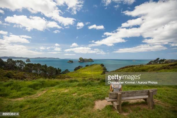 Woman sitting with child at coastline, Hahei, Coromandel, New Zealand