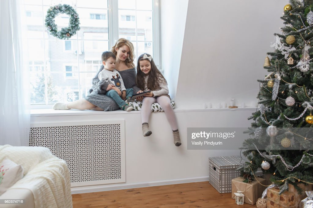 Woman sitting with children on window sill at home during Christmas : Stock Photo