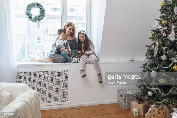 Woman sitting with children on window sill at home during Christmas