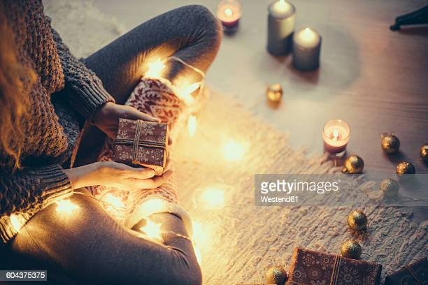 woman sitting with christmas present and fairy lights on the carpet - ギフトラウンジ ストックフォトと画像