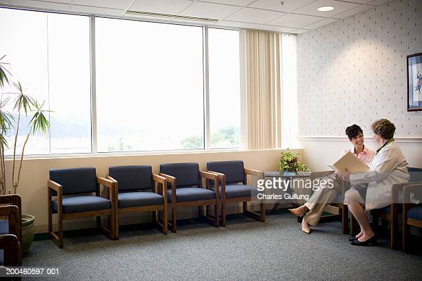 Woman sitting with doctor in doctor's waiting room, talking