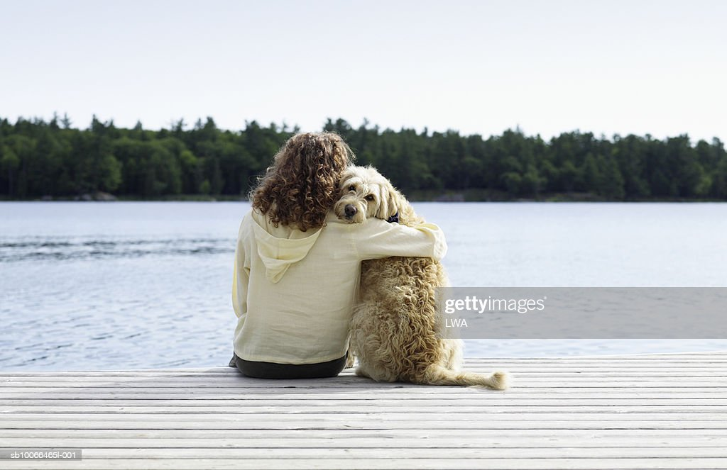 Woman sitting with dog on jetty, rear view : Stock Photo