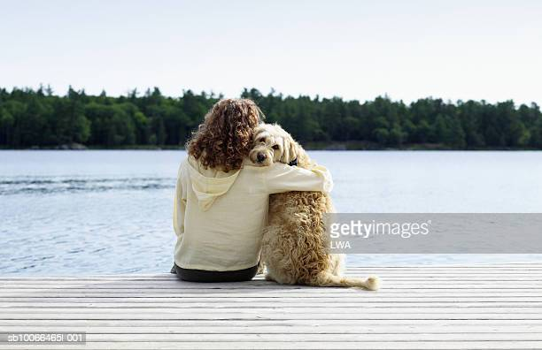 woman sitting with dog on jetty, rear view - hund stock-fotos und bilder