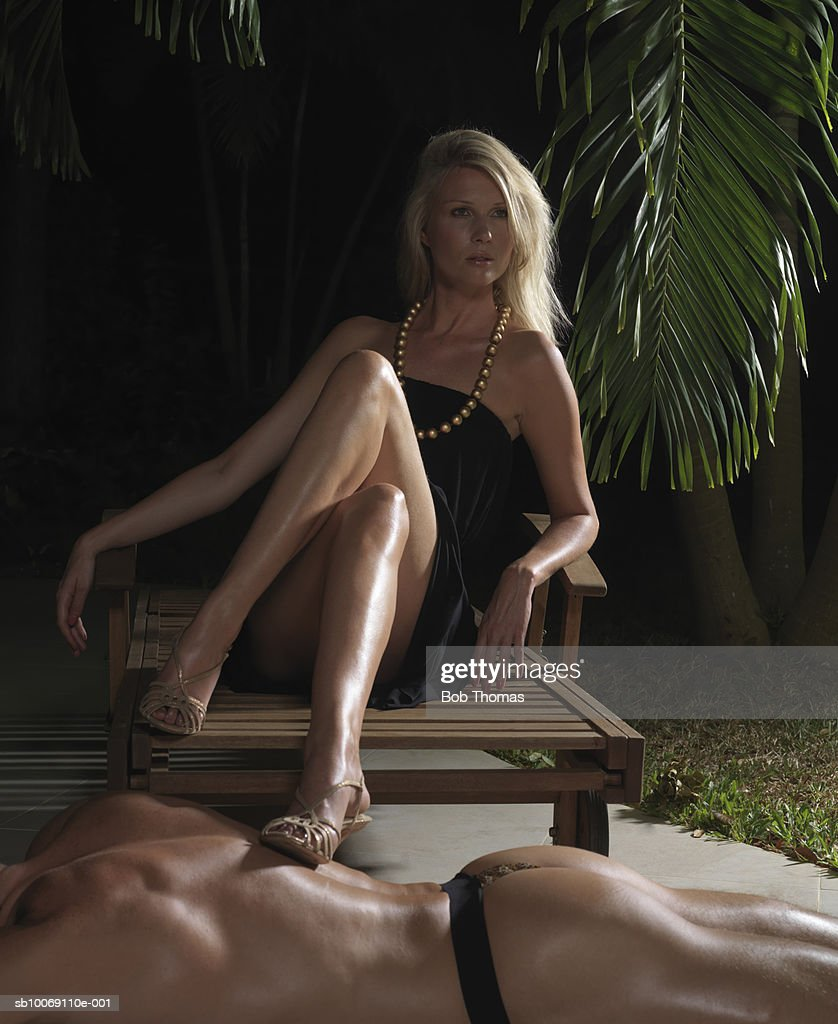 Woman sitting with foot on man's back, looking away : Stockfoto
