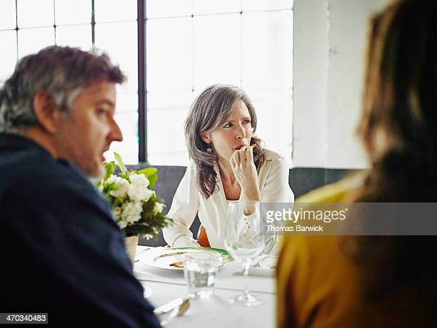 Woman sitting with friends at dinner party